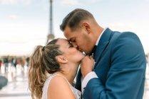 Жених в синем костюме и невеста в белом свадебном платье страстно целуются с Эйфелевой башней на заднем плане в Париже — стоковое фото