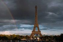 Mächtiger Eiffelturm inmitten grüner Pflanzen und Gebäude mit bewölktem Himmel und Regenbogen im Hintergrund in Paris — Stockfoto