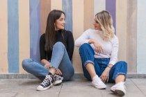 Sorrindo positivo mulheres elegantes apoiando-se uns nos outros enquanto sentado perto da calçada perto de parede de rua listrada olhando um para o outro — Fotografia de Stock