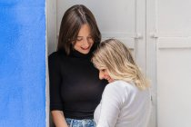 Side view of happy gentle caring girlfriends in stylish outfit embracing while standing near door looking at each other — Stock Photo