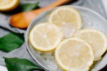 Сверху куски свежего лимона в миске со льдом украшены зелеными листьями на размытом фоне — стоковое фото