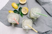 Смачний лимонад у стильних банках з барвистими соломинками для пиття на розмитому фоні. — стокове фото