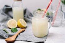 Смаковий лимонад у пляшці та стильній банці на серветці на столі. — стокове фото