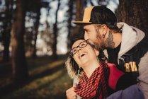 Одягнений чоловік обіймає веселу жінку біля лісу на невиразному тлі. — стокове фото