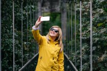 Щаслива жінка - мандрівниця, що влітку їде на висячому мосту. — стокове фото