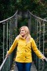 Весела жінка - туристка, що стоїть на висячому мосту влітку. — стокове фото
