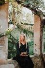 Femme en robe longue vêtements avec les yeux fermés et tenant bol musical en métal tout en étant assis dans les ruines du vieux château dans un lieu historique — Photo de stock