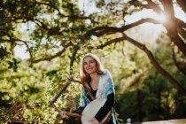 Музыкант, носящий шарф на плечах, держа лиру и стоя зеленый сад в летний день в задней освещении — стоковое фото