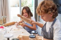 Male and female little kids in aprons smiling while rolling brown dough with pin on table at modern kitchen — Stock Photo