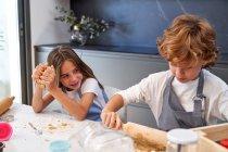 Männliche und weibliche kleine Kinder in Schürzen lächeln beim Rollen von braunem Teig mit Nadel auf dem Tisch in der modernen Küche — Stockfoto