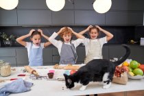 Shocked male and female kids in aprons looking at cat eating ingredients on table at modern kitchen — Stock Photo