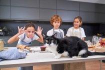 Симпатичные дети в фартуках смотрят и смеются над кошкой на столе на современной кухне — стоковое фото