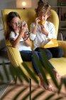 Розумна сестра і брат сидять у жовтому кріслі, слухаючи мобільний телефон і розмовляючи по телефону у вітальні. — стокове фото