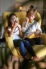 Smart sorella e fratello seduti in poltrona gialla durante la navigazione cellulare e parlare al telefono vintage in soggiorno — Foto stock