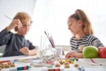 Концентрированные девочка и мальчик в повседневной живописи одежды с акварелью, сидя за столом дома — стоковое фото