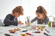 Ragazza concentrata e ragazzo in abiti casual pittura con acquerello mentre seduto a tavola a casa — Foto stock