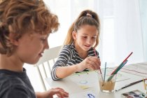 Concentrated girl and boy in casual outfits painting with watercolor while sitting at table at home — Stock Photo