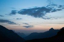 Increíble paisaje de siluetas de montañas rocosas a la luz del atardecer en Suiza - foto de stock
