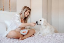 Content blonde pregnant woman sitting on bed with crossed legs holding bowl of food while Labrador dog putting paws near and looking at meal — Stock Photo