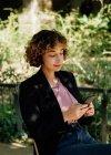 Оптимистичная женщина с вьющимися волосами сидит на стуле на террасе и просматривает смартфон в солнечный день в сельской местности — стоковое фото