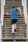 Rückansicht von unten von einem Sportler in Sportkleidung, der die Treppe hochläuft — Stockfoto