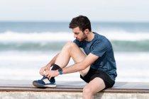 Черноволосый бородатый спортсмен в синей футболке и шортах сидит на заборе и завязывая шнурки с голубым морем и небом на размытом фоне — стоковое фото