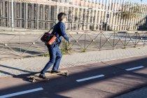 Contenuto elegante uomo d'affari in tuta di classe su longboard guida lungo la strada asfaltata in pieno giorno — Foto stock