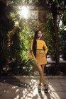 Вид сбоку азиатской женщины с длинными темными волосами в желтой рубашке и короткой юбке, стоящей в красивом саду и смотрящей в камеру — стоковое фото