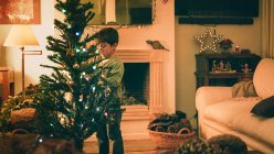 Мальчик украшает елку вечером — стоковое фото