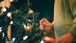Cropped image of Boy decorating Christmas tree in evening — Stock Photo