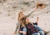 Женщина, держащая шляпу, нежно обнимает подругу и смотрит в сторону природы — стоковое фото
