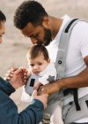 Multiracial fathers cuddling little baby outdoors — Stock Photo