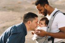 Многорасовые отцы обнимаются и целуют маленького ребенка на открытом воздухе — стоковое фото