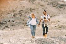 Веселый мужчина, несущий маленького ребенка и держащийся за руки с блондинкой женой во время прогулки по песчаной пустыне — стоковое фото