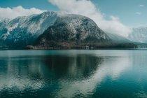Потрясающий пейзаж волнистого озера, отражающего яркое облачное небо и снежные горы в Халлштатте — стоковое фото