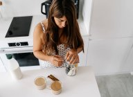 Brown-haired lady checking cinnamon and sugar from jar on white table with cups of coffee at modern kitchen — Stock Photo