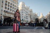Femme asiatique avec valise debout sur le trottoir près de la route et regardant loin tout en visitant la ville le jour ensoleillé — Photo de stock