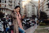 Heureuse femme asiatique avec smartphone souriant et regardant la caméra tout en étant assis sur la valise sur le trottoir sur la rue de la ville — Photo de stock