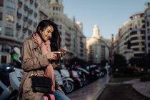Pleine longueur femme asiatique heureuse avec smartphone souriant et regardant loin tout en étant assis sur la valise sur le trottoir sur la rue de la ville — Photo de stock
