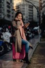 Femme asiatique avec smartphone souriant et regardant la caméra tout en étant assis sur la valise sur le trottoir sur la rue de la ville — Photo de stock