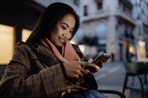 Mulher asiática sorrindo e navegando nas redes sociais no smartphone enquanto descansa no restaurante de rua à noite — Fotografia de Stock