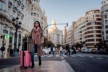 Mujer asiática con maleta de pie en el pavimento cerca de la carretera y mirando hacia otro lado mientras visita la ciudad en un día soleado - foto de stock