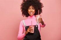Щаслива чорна жінка з одноразовою чашечкою алкоголю стоїть навпроти рожевого фону. — стокове фото