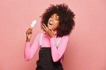 Дивна жінка з морозивом на паличці дивиться на камеру. — стокове фото