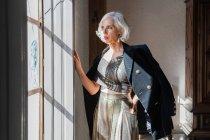 Senior elegant woman against rustic interior in country house — Stock Photo