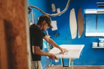 Craftsman making surf board in workshop — Stock Photo