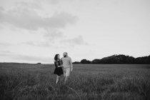Alegre casal jovem romântico de mãos dadas e caminhando no campo verde à beira-mar ao pôr-do-sol com céu nublado — Fotografia de Stock