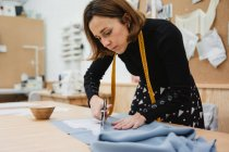 Woman using sharp scissors to cut garment detail from fabric while sitting at table in tailor workshop — Stock Photo