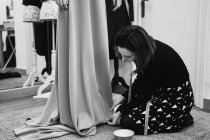 Dressmaker kneeling on carpet and fitting skirt of custom gown while working in professional studio — Stock Photo