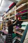 Vista lateral da mulher adulta vasculhando a prateleira ao selecionar pedaço de pano para o trabalho na sala de armazenamento da oficina de alfaiate — Fotografia de Stock